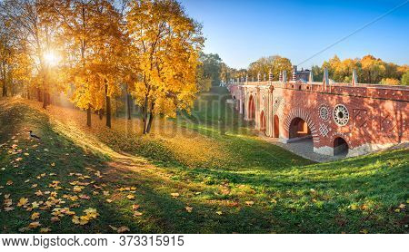Brick Bridge Over A Ravine In Tsaritsyno Park In Moscow Among Colorful Autumn Trees And Leaves On Th