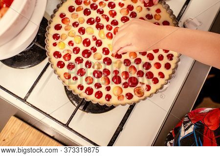 Young Boy Is Cooking And Baking Cherry Pie With Almond Slices With His Mamm