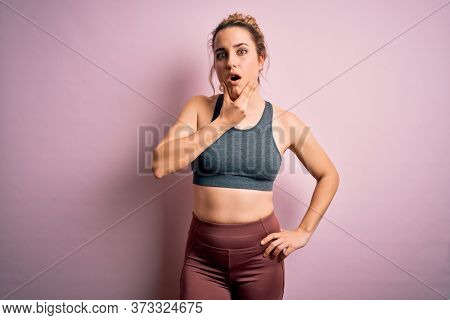 Young beautiful blonde sportswoman doing sport wearing sportswear over pink background Looking fascinated with disbelief, surprise and amazed expression with hands on chin