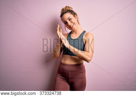 Young beautiful blonde sportswoman doing sport wearing sportswear over pink background clapping and applauding happy and joyful, smiling proud hands together