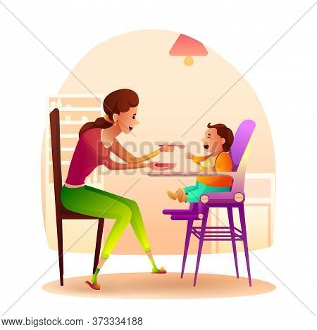Young Smiling Mother With Spoon Feeds Little Baby Sitting In Highchair At Home Kitchen. Happy Family