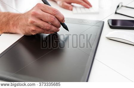 Close-up Of Person Using Digital Drawing Tablet And Stylus On White Office Desk