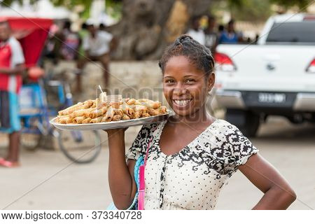 Toliara, Madagascar - January 10th, 2019: A Local Young Malagasy Woman Selling Nem - Eggrolls, Smili