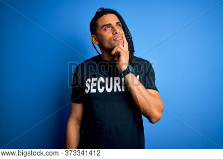 Young african american afro safeguard man with dreadlocks wearing security uniform serious face thinking about question, very confused idea