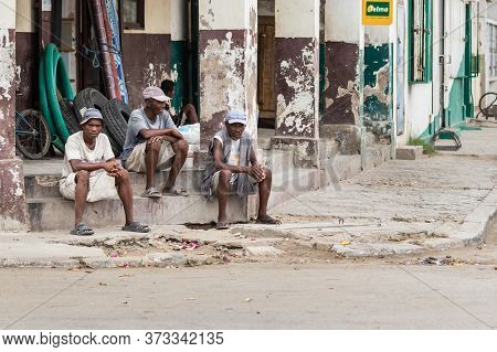 Toliara, Madagascar - January 10th, 2019: Three Construction Malagasy Workers Taking A Break In A Co