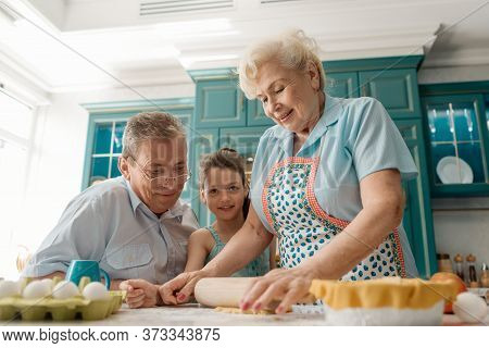 Granny Rolls Out The Dough, While Grandpa And Granddaughter Watching The Process