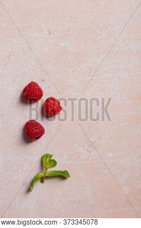 Three Raspberry And Mint Leaf On Pink Concrete Background. Concept Of Ingredients Picture. Top View,