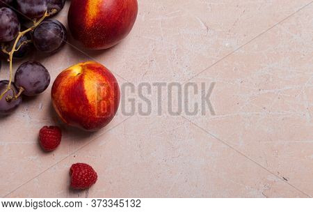 Copy Space With Nectarines And Raspberry On Pink Concrete Background