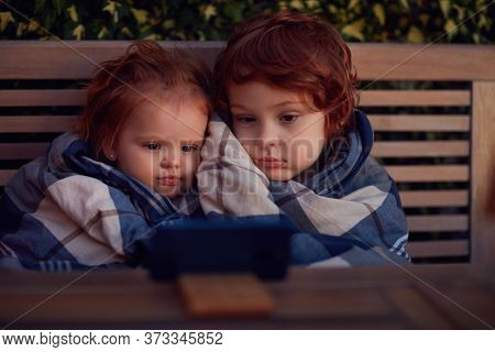 Cute Toddler Siblings Covered In Blanket, Watching Cartoons On The Phone At Summer Evening