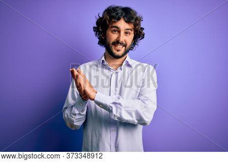 Young handsome business man with beard wearing shirt standing over purple background clapping and applauding happy and joyful, smiling proud hands together