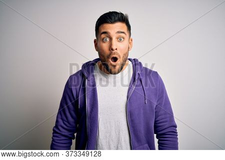 Young handsome man wearing purple sweatshirt standing over isolated white background afraid and shocked with surprise expression, fear and excited face.