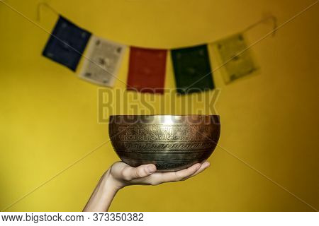 The Hand Holds A Tibetan Singing Bowl Against The Background Of A Yellow Wall With Tibetan Flags