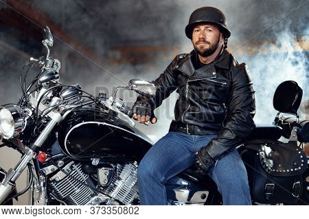 Biker Man In Leather Jacket And Helmet Sitting On His Motorcycle