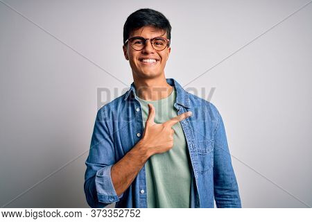 Young handsome man wearing casual shirt and glasses over isolated white background cheerful with a smile of face pointing with hand and finger up to the side with happy and natural expression on face
