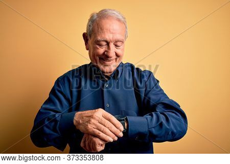 Grey haired senior man wearing casual blue shirt standing over yellow background Checking the time on wrist watch, relaxed and confident