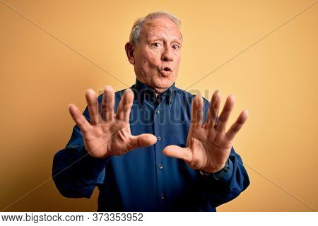 Grey haired senior man wearing casual blue shirt standing over yellow background Moving away hands palms showing refusal and denial with afraid and disgusting expression. Stop and forbidden.