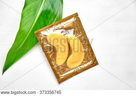 Gold Collagen Eye Mask Or Patches On A White Background With Green Leaves. Skin Care And Beauty Conc