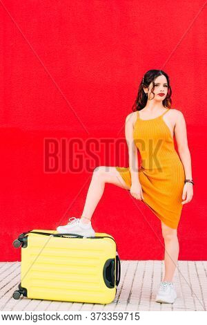 Young Woman Stepping On A Yellow Suitcase