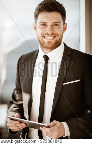 Business concept. Happy smiling young businessman standing in office holding wireless touchpad tablet computer. Man in suit indoors using internet device on glass window background.