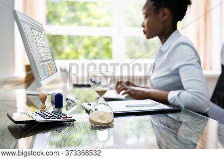 Black Accountant Woman Working With Invoice And Hourglass
