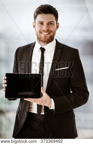 Business concept. Happy smiling young businessman standing in office demonstrating wireless touchpad tablet computer. Man in suit indoors using internet device on glass window background.