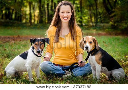 A beautiful woman and his dogs posing outside poster