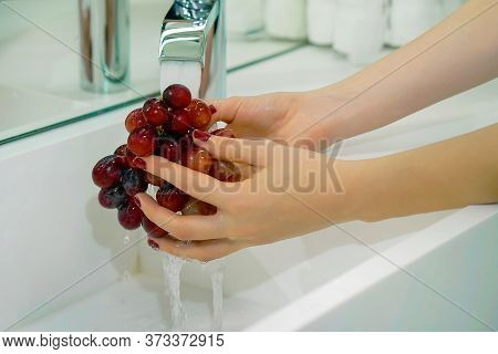 Female Hands Wash Black Grapes Under The Tap. Cook Woman Washes A Bunch Of Black Grapes Under The Wa