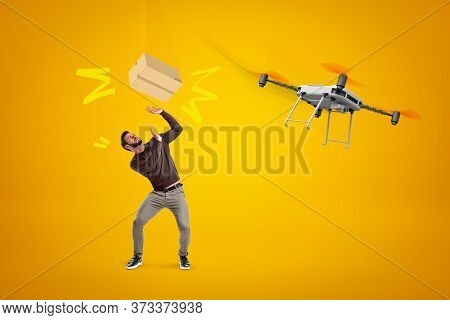 Young Man In Casual Clothes Trying To Catch Cardboard Box Dropped Off Delivery Drone On Amber Backgr
