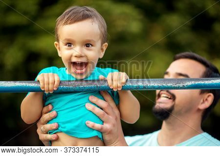 Happy Toddler Boy Doing Pull Ups Exercise, Child Smiling Happily Having Pulled Up On Steel Bar Outdo