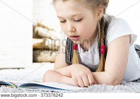 Cute Little Girl Is Reading A Book On A Carpet In An Apartment
