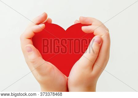 Closeup Of Paper Heart In Little Hands Of Child On White Background. Red Heart In Hands On White.