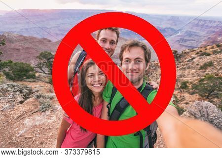 No more selfies. Social distancing obligatory, gatherings forbidden at outdoor hiking nature parks. Group of three friends hikers with red blocked sign overlay.