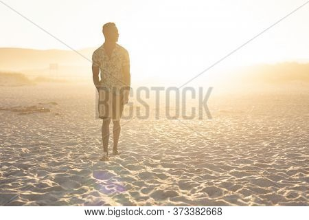 An African American man enjoying free time on beach on a sunny day, standing on sand with sun shining behind him, wearing a Hawaiian shirt. Relaxing summer vacation.