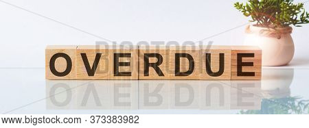 Overdue Is A Word Written In Black Letters On Wooden Cubes Located On A White Mirror Surface. The In