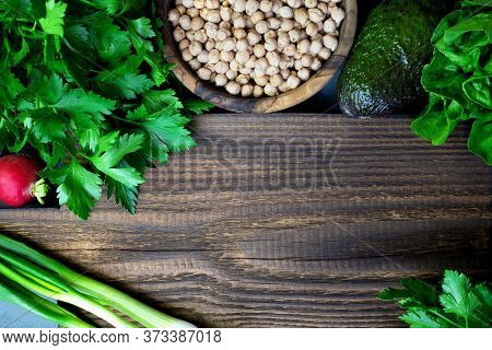 Green Vegetables And Lentils Around A Rustic Of Wooden Cutting Board. Place For Text. Cooking Health