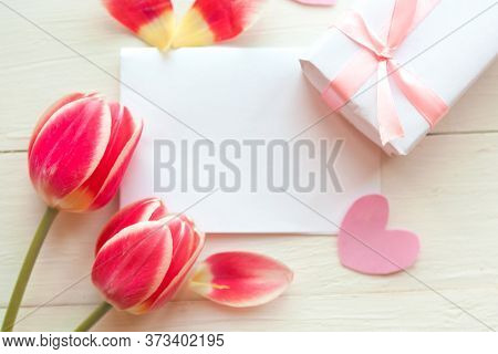 Flat Lay Photo With Gift Box And Red Tulips On Wooden Background. Beautiful Mother's Day, Women's Da