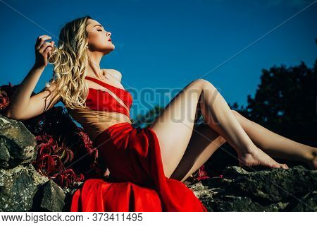 Sensual Beautiful Blonde Woman Posing Outside In Red Dress. Girl With Long Curly Hair