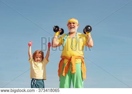 Grandfather And Child Do Morning Exercise. We Exercise Every Day. Grandfather And Child Lifting Dumb