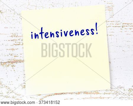Yellow Sticky Note On Wooden Wall With Handwritten Inscription Intensiveness