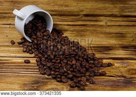 Roasted Coffee Beans Spill Out Of Cup On Wooden Table