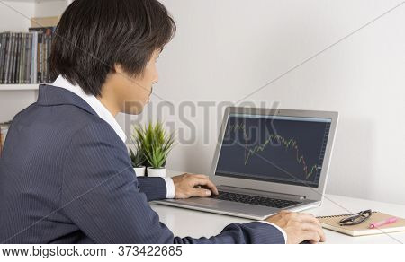 Young Asian Forex Trader Or Investor Or Businessman In Suit Trading And Looking Forex Charts Or Stoc