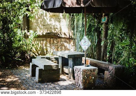 Outdoor Old Wooden Bench In Smoking Area Zone.among The Green Trees