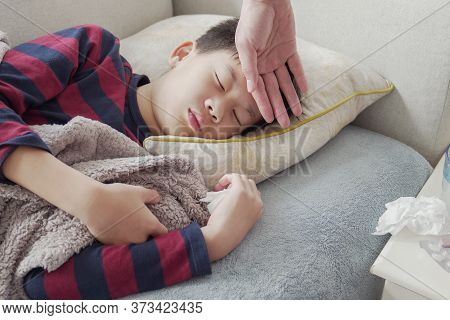 Parent Hand Checking On Sick Preteen Resting On Sofa With Medication At Home, Heath Care Concept