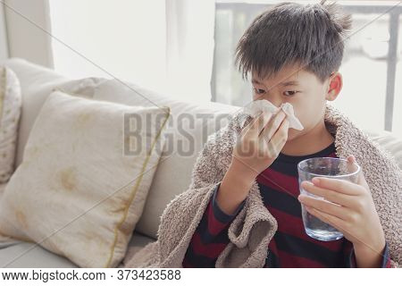 Mixed Asian Sick Preteen Boy Blowing Nose And Holding Glass Of Water At Home, Heath Care Concept