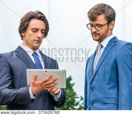 Confident businesspersons in formal wear having conversation about banking and financial markets in front of office building.