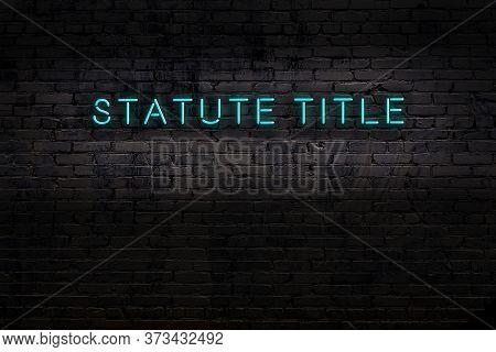 Neon Sign On Brick Wall At Night. Inscription Statute Title