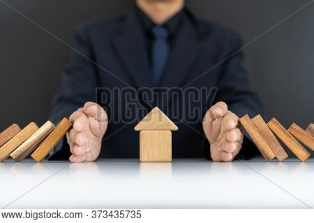 The Concept Of Home Insurance.the Hands Of Businessmen Or Homeowners That Are Blocking Domino's Fall