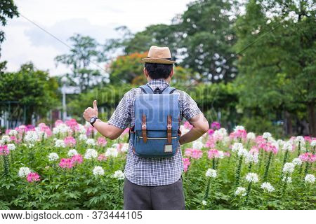 Young Man Tourists Backpack Are Standing Thumbs Up For Great Performances. At Spider Flower Garden.