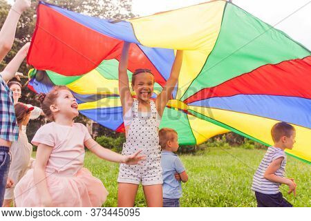 Cheerful Preteen Girl Holding Colorful Canopy Over Kids