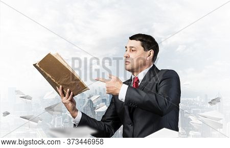 Senior Businessman Finger Pointing Into Open Book. Man In Business Suit And Tie Standing On Cityscap